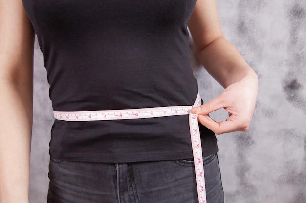 Молодая девушка измеряет обхват живота на сером