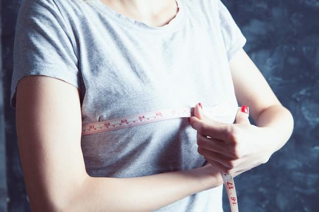 Молодая девушка измеряет свою грудь