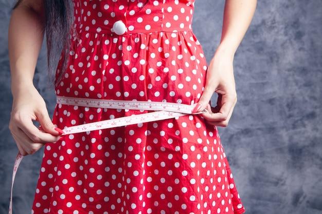 측정 테이프로 허리를 측정하는 어린 소녀