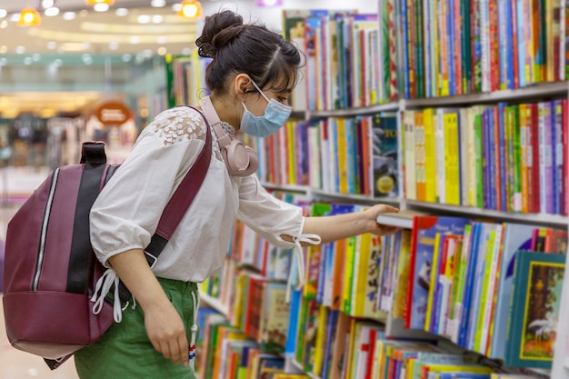 Young girl in a medical mask chooses a book in a bookstore. knowledge and education. precautions during the coronavirus pandemic.
