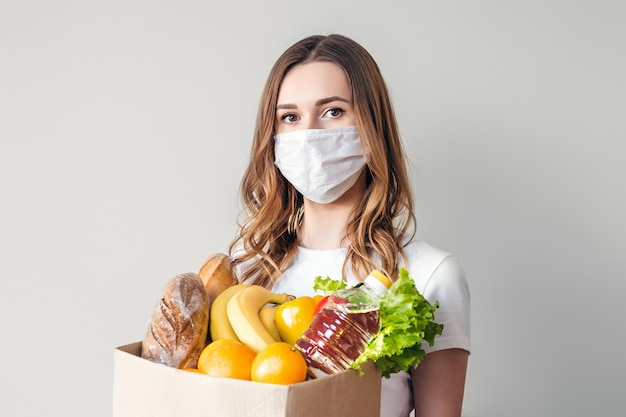 Young girl in a medical mask holds a cardboard box with vegan food, fruits and vegetables