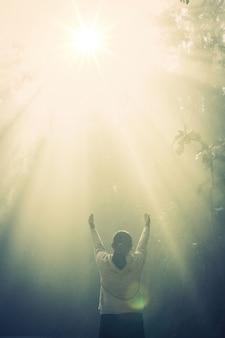 Молодая девушка медитировать в зеленом лесу с солнечным светом
