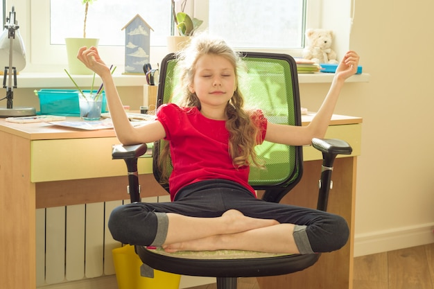 Young girl meditates at home on chair