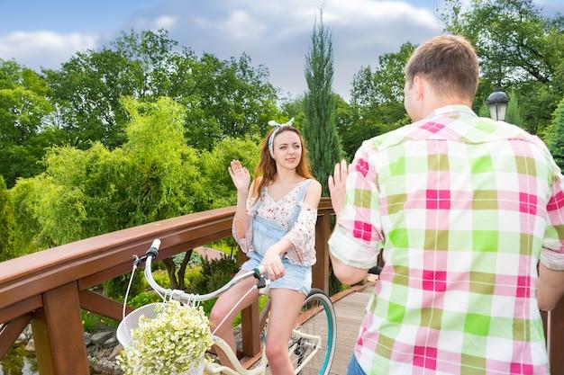 Молодая девушка встречает мальчика в зелено-красной клетчатой рубашке во время езды на велосипеде с цветами в корзине по пешеходному мосту в красивом парке