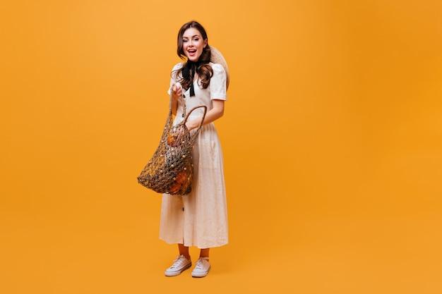 Giovane ragazza in abito midi con cappello di paglia sulla schiena sta mettendo l'arancia nella borsa di stringa su sfondo isolato.