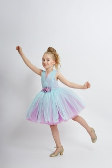 Young girl miss beauty in a beautiful dress. children's cosmetics and makeup. girl posing