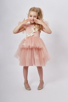 Young girl miss beauty in a beautiful dress. children's cosmetics and makeup
