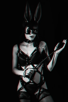 Young girl mistress in leather harness and bunny mask holds flogger whip in her hands for bdsm sex. black and white with glitch effect