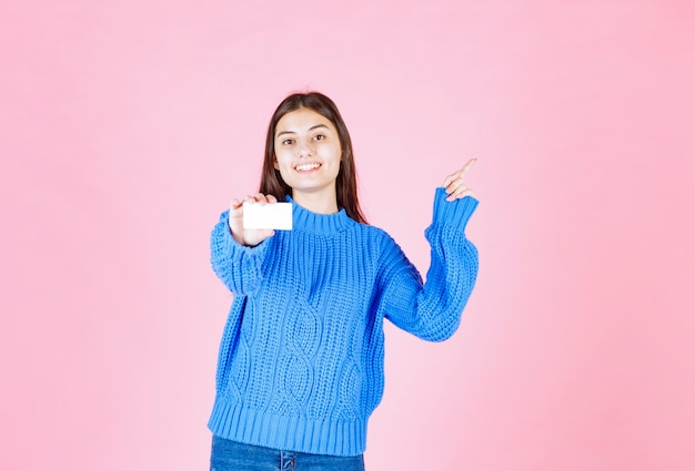 Young girl model holding a card on pink wall.