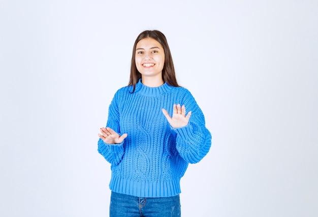 Молодая девушка модель в синем свитере стоя и позирует на бело-сером.