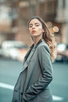 若い女の子、モデル、カメラを見て、アメリカのジャケットを着ています。通りの背景に。