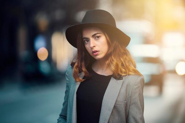 Молодая девушка, модель, смотрит в камеру, в блейзере и шляпе. на фоне улицы и автомобилей.