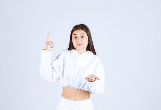 Модель молодой девушки указывая вверх и показывая руку.