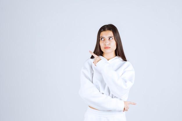 Модель молодой девушки указывая вверх указательными пальцами.