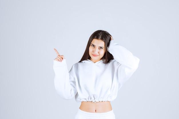 검지 손가락으로 가리키는 어린 소녀 모델.
