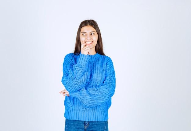 Молодая девушка модель улыбается и смотрит в сторону.