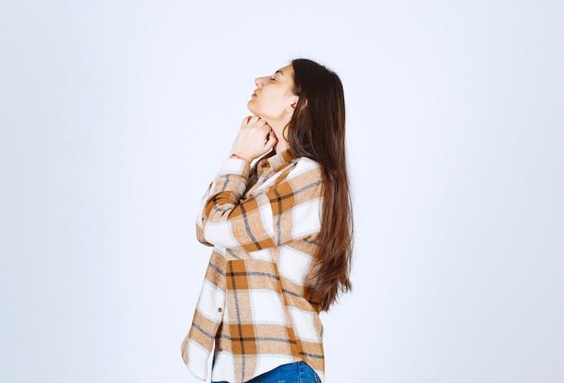 白灰色の壁に立っている若い女の子モデル。 無料写真