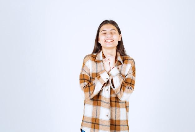 白灰色の壁に立っている若い女の子モデル。