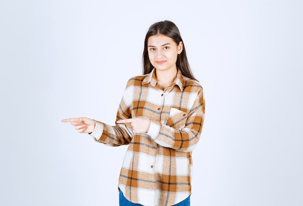 Young girl model standing and pointing away on white-gray wall.