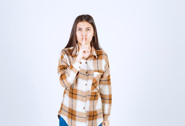Giovane ragazza modello in piedi e mostrando segno silenzioso.