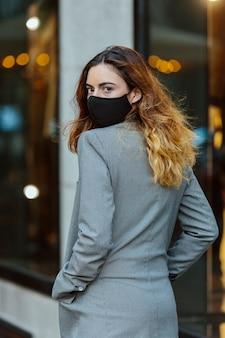 Молодая девушка, модель, идет в обратном направлении, смотрит в камеру, в американской куртке и маске.