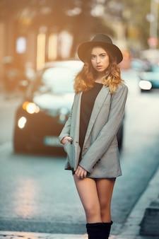 Молодая девушка, модель, в блейзере и шляпе, гуляет по улице и фоне автомобилей.