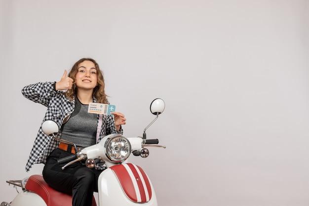 Giovane ragazza sul motorino che tiene il biglietto che dà i pollici in su