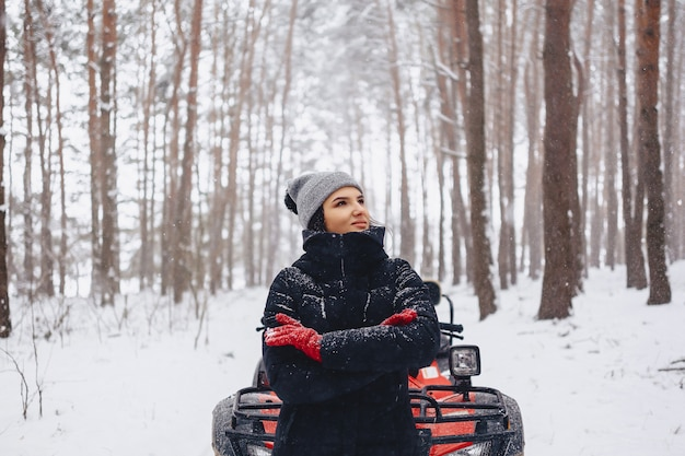 Young girl on a motorcycle rides in snow-covered pine forest in winter