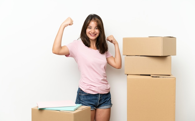 Young girl moving in new home among boxes celebrating a victory