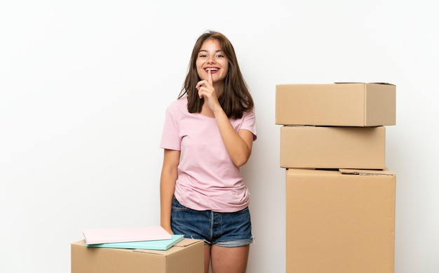 Young girl moving in new home among boxes doing silence gesture