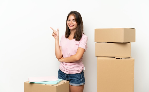 Young girl moving in new home among boxes pointing finger to the side