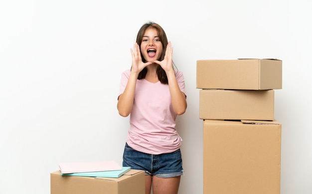 Young girl moving in new home among boxes shouting with mouth wide open