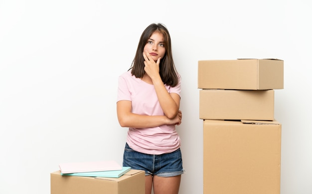Young girl moving in new home among boxes thinking an idea