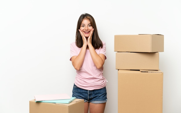 Young girl moving in new home among boxes with surprise facial expression