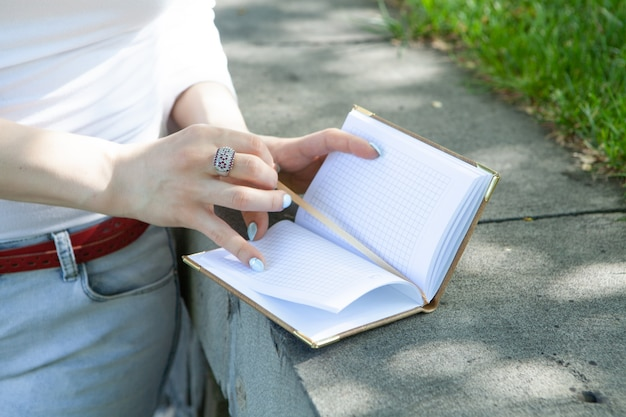 Young girl in nature opened a diary. take notes