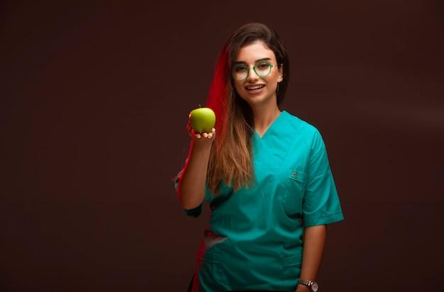 手に青リンゴを提供する少女。
