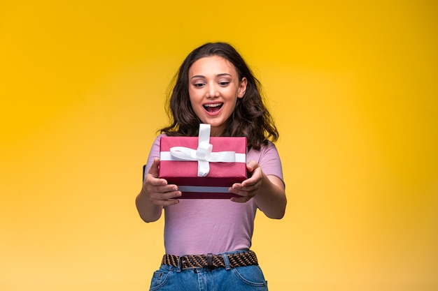 Молодая девушка предлагает красную подарочную коробку и улыбается.