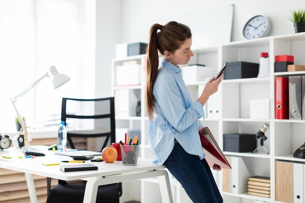 A young girl in the office is standing, leaning on a table, and is holding a phone and a folder