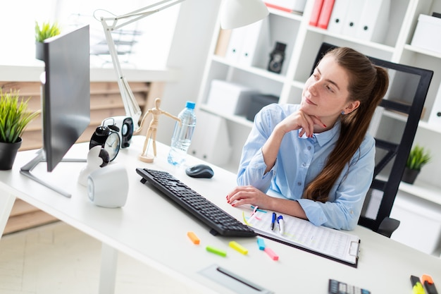 Young girl in the office sits at the computer desk.