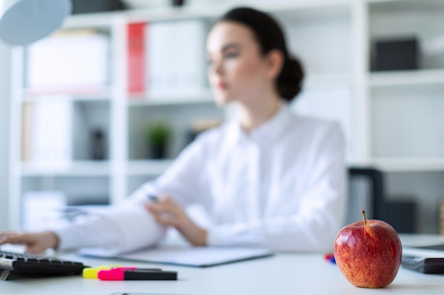 Young girl in the office with an apple. a photograph with a depth of field, a highlighted focus on an apple.