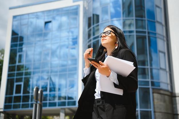 Молодая девушка офисного работника в очках, темной куртке и синей рубашке остается на городской улице возле офисного здания и держит свои документы