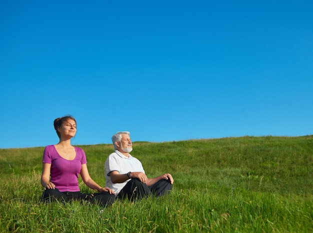 Young girl and old man meditating sitting in the field.
