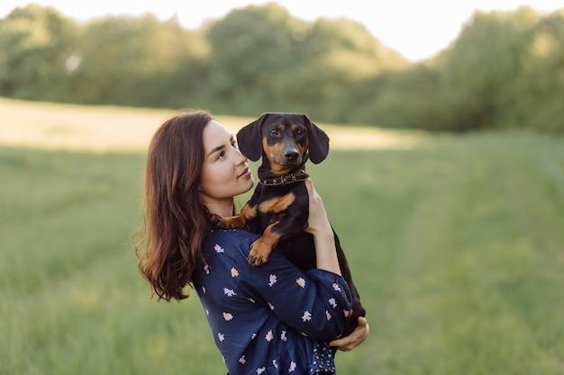 Молодая девушка на прогулке со своим щенком