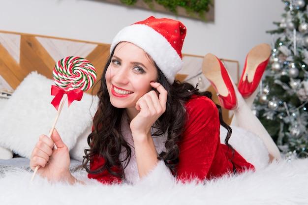 キャンディケインを保持している背景のクリスマスイブのクリスマスツリーの若い女の子。装飾されたアパートの背景に赤い美しいサンタクロースまたはエルフの衣装を着た女性。ニューイヤーコンサート
