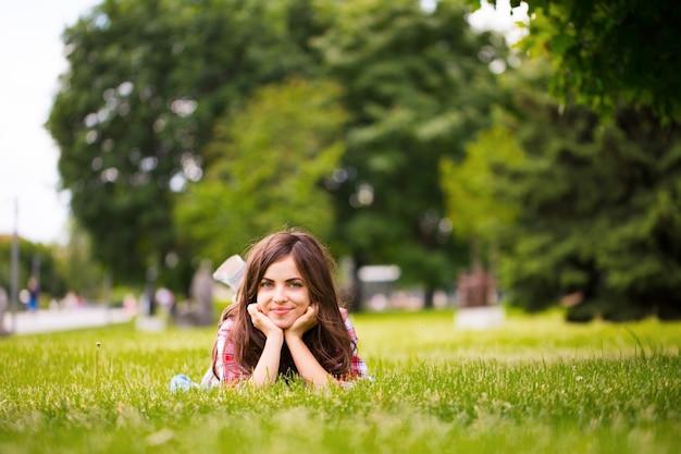 Молодая девушка на траве в парке