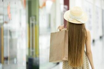 茶色のバッグと彼女の背中に若い女の子