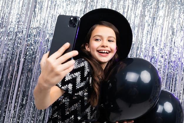 휴일에 어린 소녀는 검은 풍선 사이에서 스마트 폰으로 사진을 찍습니다
