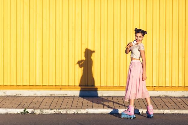 여름 날에 어린 소녀가 롤러 블레이드를 타고 노란색 벽에 아이스크림을 먹습니다.
