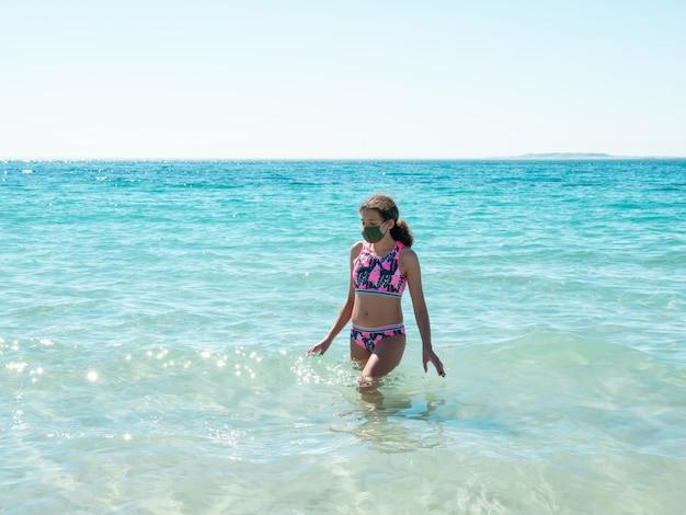 コロナウイルス病を避けるために防護マスクを着てビーチで若い女の子