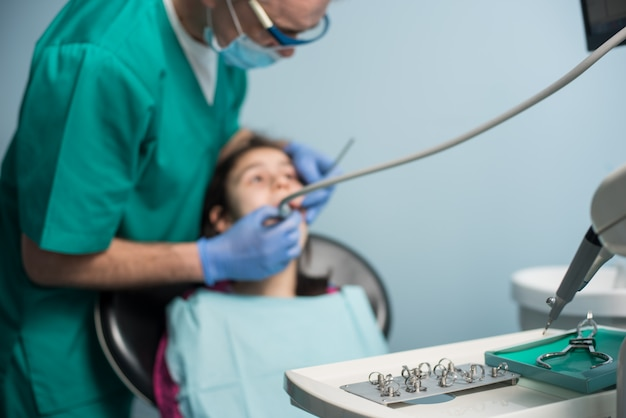 最初の歯科訪問の少女。歯科医院で患者の少女の歯を治療する上級小児歯科医
